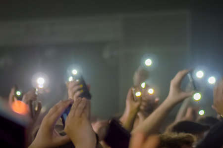 People crowd waving hands and holding smartphones with flashlights at rock concert in front of stage of nightclub. Nightlife, technology, leisure time and entertainment concept Stok Fotoğraf