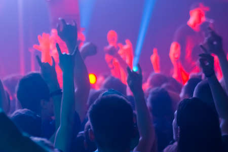 People crowd partying, raising hands up, showing sign - devils horns gesture at rock concert in front of stage of nightclub. Colorful stage lighting. Nightlife and entertainment concept Stok Fotoğraf - 166779659