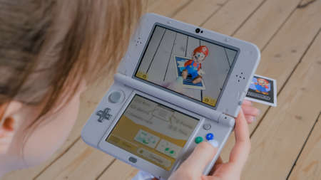 MOSCOW, RUSSIA - AUGUST 1, 2019. Woman gamer hand using grey handheld game console 3ds with augmented reality application - placing famous Nintendo character - Mario. Gaming, AR, technology concept Editöryel