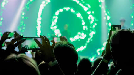 People hands silhouette taking photo or recording video of live music concert with smartphone. Crowd partying in front of stage. Photography, entertainment, technology concept