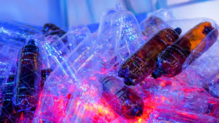 Used plastic bottle contemporary art eco installation with dynamic blue and red illumination at recycling exhibition. Environmental protection, zero waste, ecology, symbol concept Stok Fotoğraf - 166904459