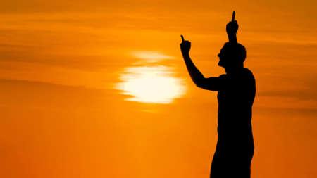 Unrecognizable man silhouette showing middle finger gesture at sunset. Rebel, punk, indecent and obscene concept Stok Fotoğraf - 166904461