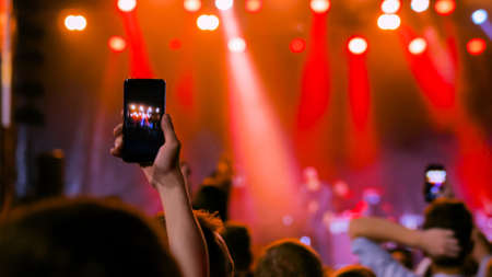 Unrecognizable people hands silhouette taking photo or recording video of live music concert with smartphone. People partying in front of the stage. Photography, entertainment and technology concept