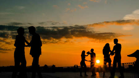 Unrecognizable people silhouette learning how to dance - on city embankment at sunset. Street dance, romantic and urban culture concept Stok Fotoğraf