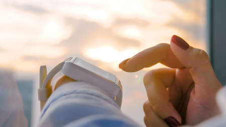 Close up: woman hand using wearable white smartwatch device against warm sunset sky - scrolling and touching. Sun lens flare, golden hour. Relax, leisure time and technology concept