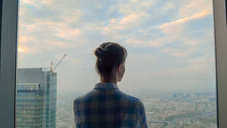 Back view of pensive woman silhouette looking at cityscape through window of skyscraper. Summer time, cloudy, daylight. Success, opportunity, sightseeing, discover and future concept