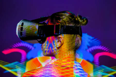 Woman using virtual reality headset, looking left at interactive technology exhibition with multicolor projector light illumination. VR, augmented reality, immersive, entertainment concept Stok Fotoğraf