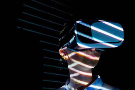 Woman using virtual reality headset and looking around at interactive technology exhibition with colorful projector light illumination. VR, augmented reality, immersive, entertainment concept Stok Fotoğraf - 166696250