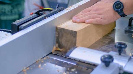 Professional man carpenter using sander machine, polishing wood product at workshop - close up. Design, handmade, woodwork, carpentry, craftsmanship, manufacturing concept