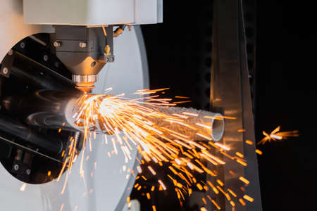 Automatic cnc laser cutting machine working with cylindrical metal workpiece with sparks at factory, plant. Metalworking, machining, industrial, equipment, technology, manufacturing concept Standard-Bild
