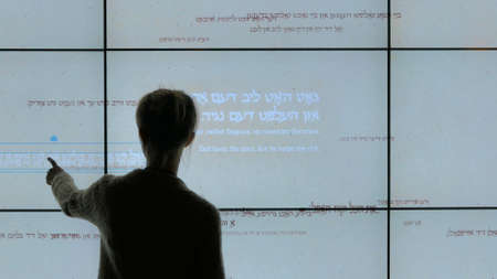 Woman using interactive touchscreen display with biblical hebrew phrases at modern jewish history museum. Education and technology concept