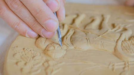 Professional male potter making clay stamp picture. Handwork, crafting and traditional arts concept Stockfoto