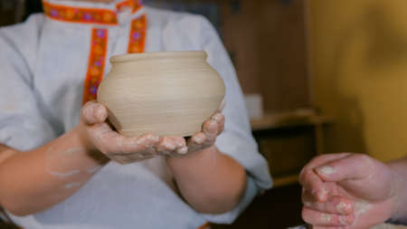 Pottery class and workshop - kid holding ceramic pot in pottery studio. Handmade, education and study concept Stockfoto