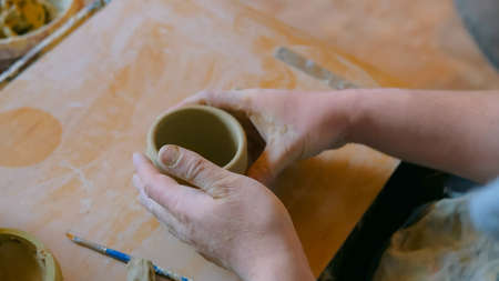 Professional male potter working in workshop, studio - making handle for ceramic mug. Handmade, small business, crafting work concept Stockfoto