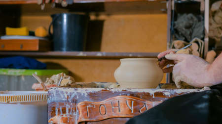 Professional male potter shaping and carving pot with special tool in pottery workshop, studio. Crafting, artwork and handmade concept