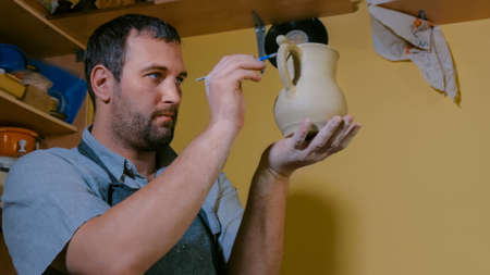 Professional male potter making ceramic jug with handle in workshop, studio. Handmade, small business, crafting work concept Stockfoto