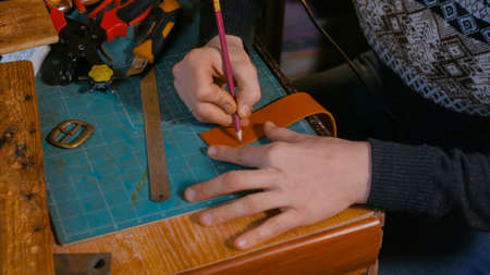 Professional male skinner, tanner working with genuine leather belt at workshop, studio. Handmade and leatherwork concept Stockfoto