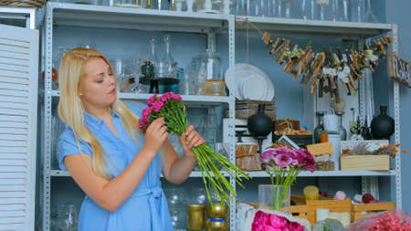 Professional woman floral artist, florist in blue dress preparing flowers - pink turkish carnations for bouquet at workshop, flower shop. Floristry, handmade and small business concept Stockfoto