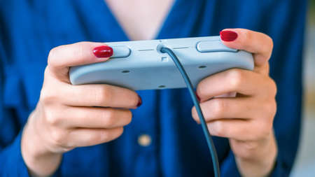 Woman using retro gaming console controller. Gaming, hobby, technology and leisure time concept Stockfoto