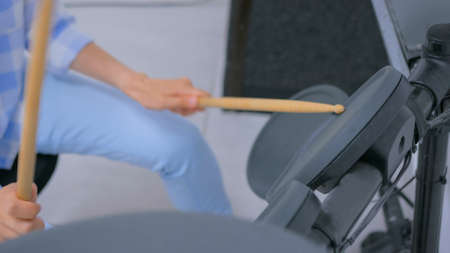 Woman learning to play on electronic drum set. Close up shot. Art, education and entertaiment concept Stockfoto