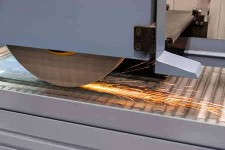 Automatic cnc surface grinding wheel machine working with sheet metal with sparks at factory, plant. Metalworking, machining, industrial, equipment, technology, manufacturing concept