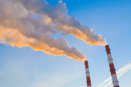 Factory smokestacks, chimneys emitting white smoke against blue sunset sky - wide angle view. Environmental pollution, ecology problems, industrial emissions, manufacturing concept Standard-Bild