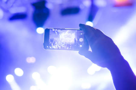 Man hands silhouette taking photo or recording video of live music concert with smartphone in front of stage of nightclub - close up, lens flare. Photography, entertainment, technology concept