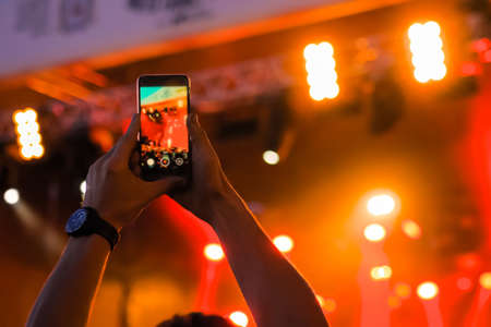 Man hands taking photo or recording video of live music concert with smartphone: close up. Bright colorful red stage lighting, lens flare. Photography, entertainment, technology concept