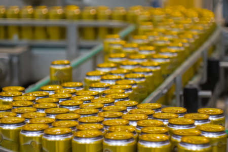 Moving yellow aluminium beer cans on conveyor belt at brewery factory, plant. Manufacturing, industrial and automated technology equipment concept Standard-Bild