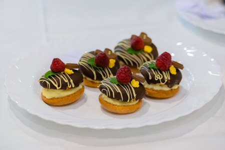 Close up: assortment of delicious fresh shortcrust tart cakes with cream, chocolate and berries on white plate for sale at restaurant, cafe, bakery. Dessert, culinary and confectionery concept