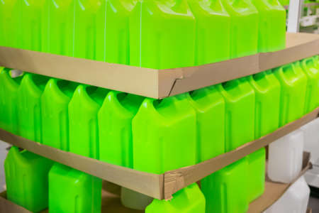 Stacks of many empty green plastic jerrycans in warehouse, market, factory or exhibition