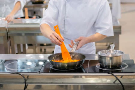 Chef hands holding silicone spatula and cooking vegetables - sliced bell pepper and onion in frying pan with oil on electric stove - front view. Professional cooking, gastronomy and food concept