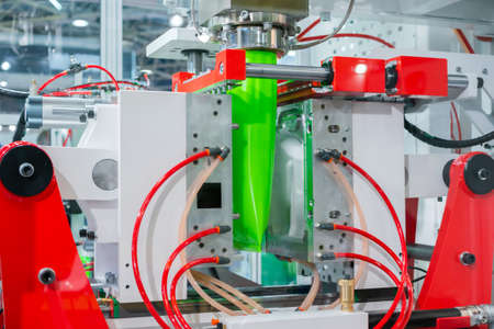 Automatic blow molding machine - manufacturing of empty green plastic jerrycans at factory, exhibition. Industry, packaging, automated technology equipment concept
