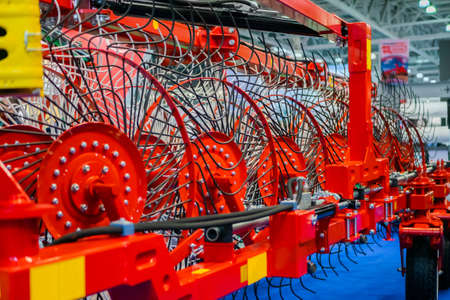 Red tractor rotary wheel hay and tedding rakes at farming exhibition, trade show. Agriculture machinery equipment concept Standard-Bild