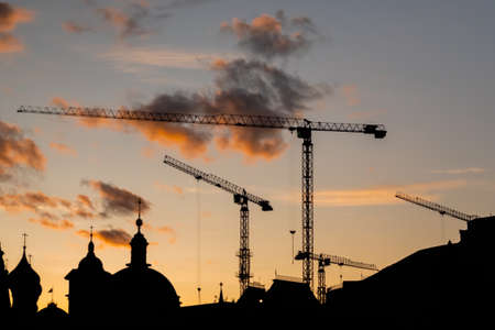 Tower cranes silhouettes and unfinished building construction against dramatic sunset warm sky. Evening time, low light. Building process, construction, engineering, industrial and development concept