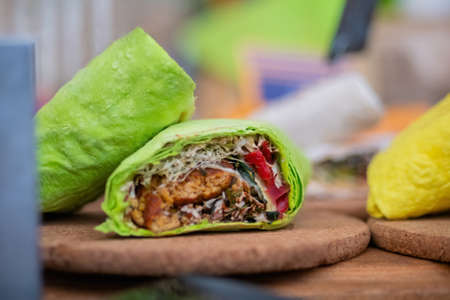 Fresh colorful green vegan doner rolls with vegetables on counter at summer local food market - close up view. Outdoor cooking, gastronomy, vegetarian, street food concept