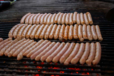 Process of grilling fresh meat sausages on big round grill at summer local food market - close up view. Outdoor cooking, barbecue, gastronomy, cookery, street food concept Standard-Bild