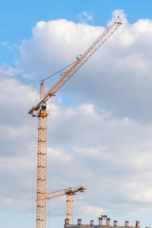 Yellow tower construction cranes against summer cloudy sky. Building process, architecture, urban, engineering, industrial and development concept Standard-Bild