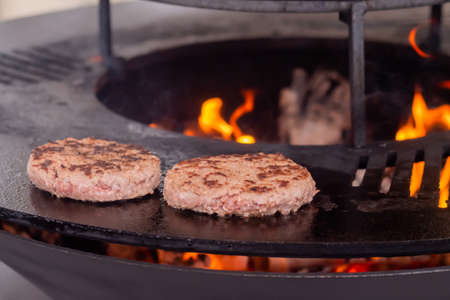 Process of grilling fresh meat cutlets for burgers on brazier with hot flame at summer local food market - close up view. Outdoor cooking, gastronomy, cookery, street food concept Standard-Bild