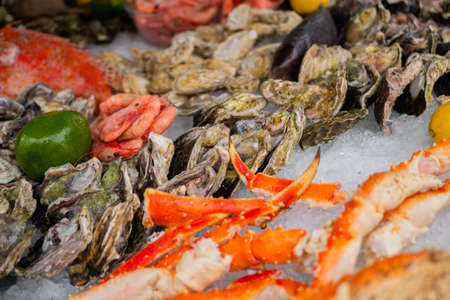 Raw crab claws, oysters, shrimp, avocado, lemon, clam on counter at summer local fish market - close up. Retail, gastronomy and seafood concept