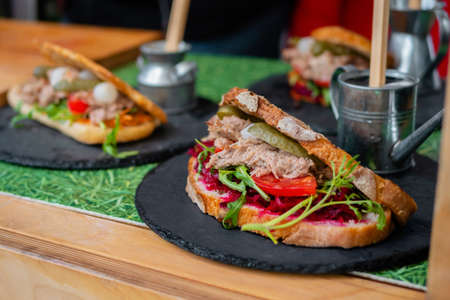 Sandwich with tuna, arugula, pickle, tomato, beetroot on counter at summer local food market - close up. Gastronomy, street food, mediterranean and Italian dish concept Standard-Bild
