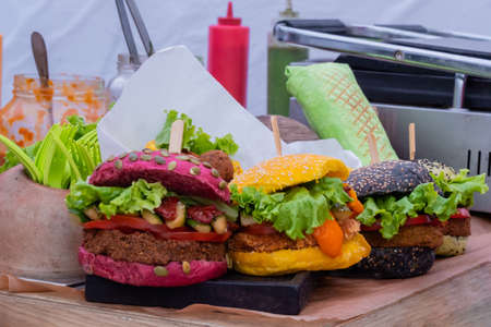 Fresh colorful vegan burgers with vegetables on counter at summer local food market - close up view. Outdoor cooking, gastronomy, vegetarian, street food concept Standard-Bild