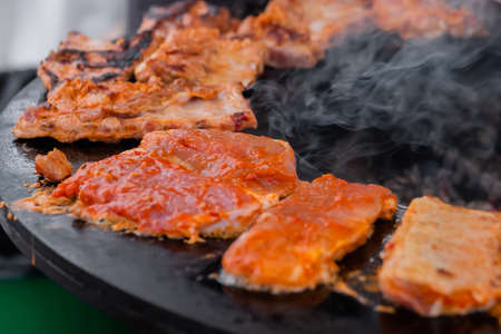 Process of cooking fresh juicy meat steaks on brazier at summer local food market - close up view. Outdoor cooking, gastronomy, cookery, street food concept