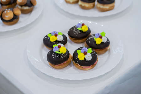 Assortment of delicious fresh shortcrust tart cakes with cream and chocolate on white plate for sale at restaurant, cafe, bakery. Dessert, culinary, sweet food and confectionery concept Standard-Bild