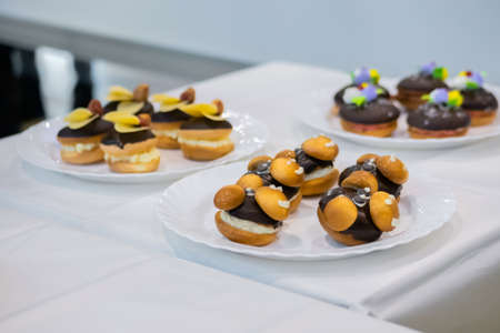 Assortment of delicious fresh shortcrust tart cakes with chocolate and sweet mushrooms on white plate for sale at restaurant, cafe. Dessert, culinary and confectionery concept