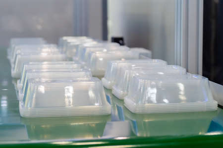 Stack of polypropylene food containers on conveyor belt of automatic plastic injection molding machine at exhibition, factory. Industry, manufacturing, automated technology concept