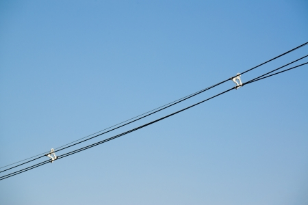megawatts: parallel of power cable lines and cable divider with blue sky background Stock Photo