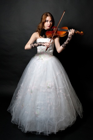 performing: Girl in white dress with violin on black background