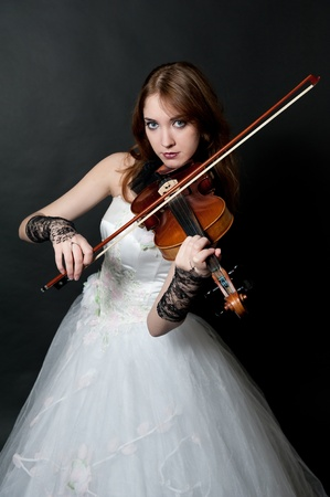 Girl in white dress with violin on black background