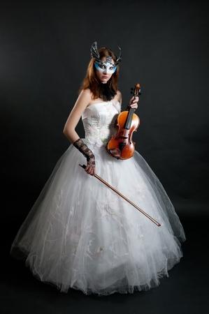 musicality: Ragazza in abito bianco e maschera con violino su sfondo nero Archivio Fotografico